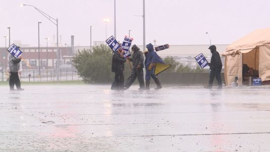 Striking John Deere employees continue to picket company during rainy weather